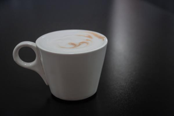 белая чашка кофе с молоком на черном фоне