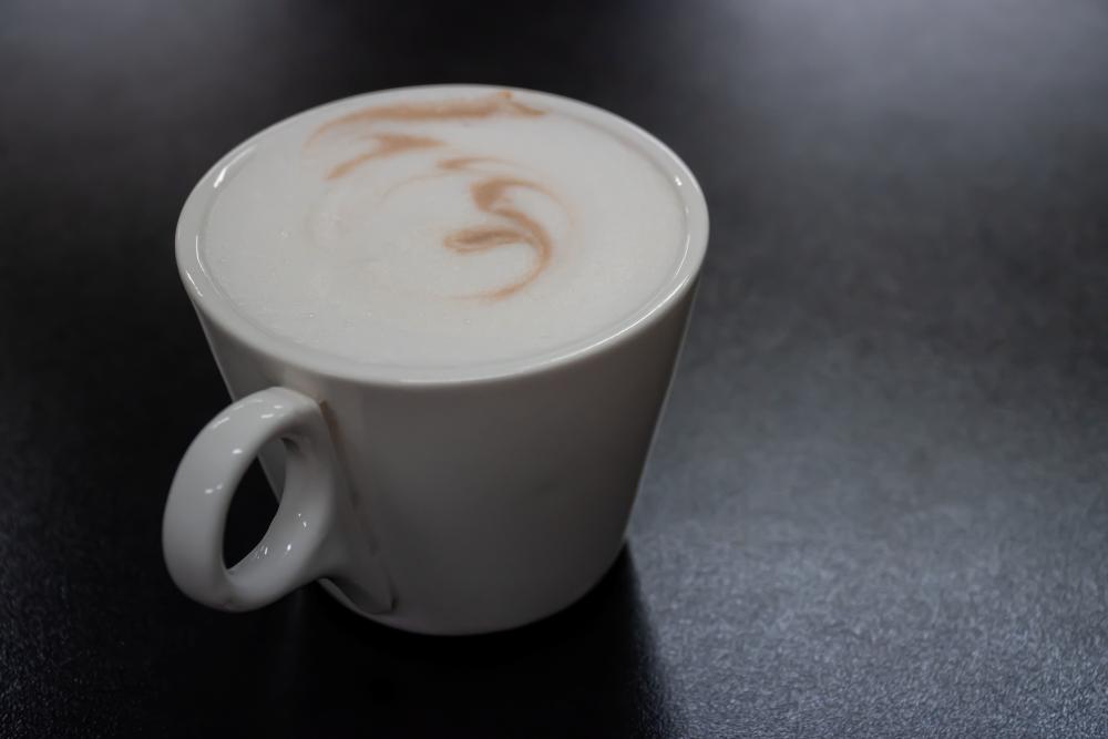 белая чашка с молочным кофе на черном фоне