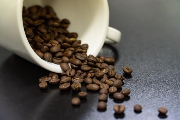 белая чашка кофе с зернами лежащая