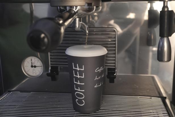 черный стакан кофе возле кофемашины