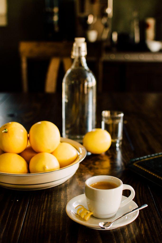 лимоны и белая чашка кофе на столе рядом с бутылкой