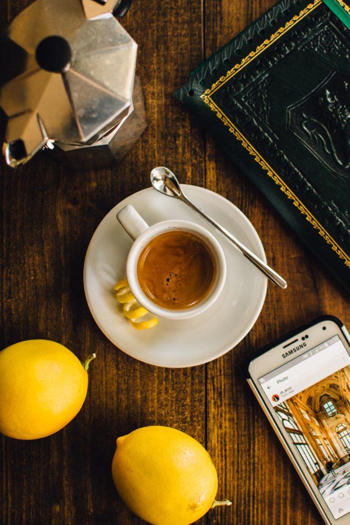 кофе с лимоном на столе рядом с кофеваркой, лимоном и телефоном
