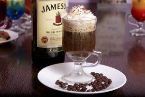 ирландский кофе в специальном бокале с кремом на белой тарелке с насыпанными кофейными зернами на фоне ирландского виски