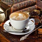чашка кофе возле старинного кувшина и старинной арабской книги