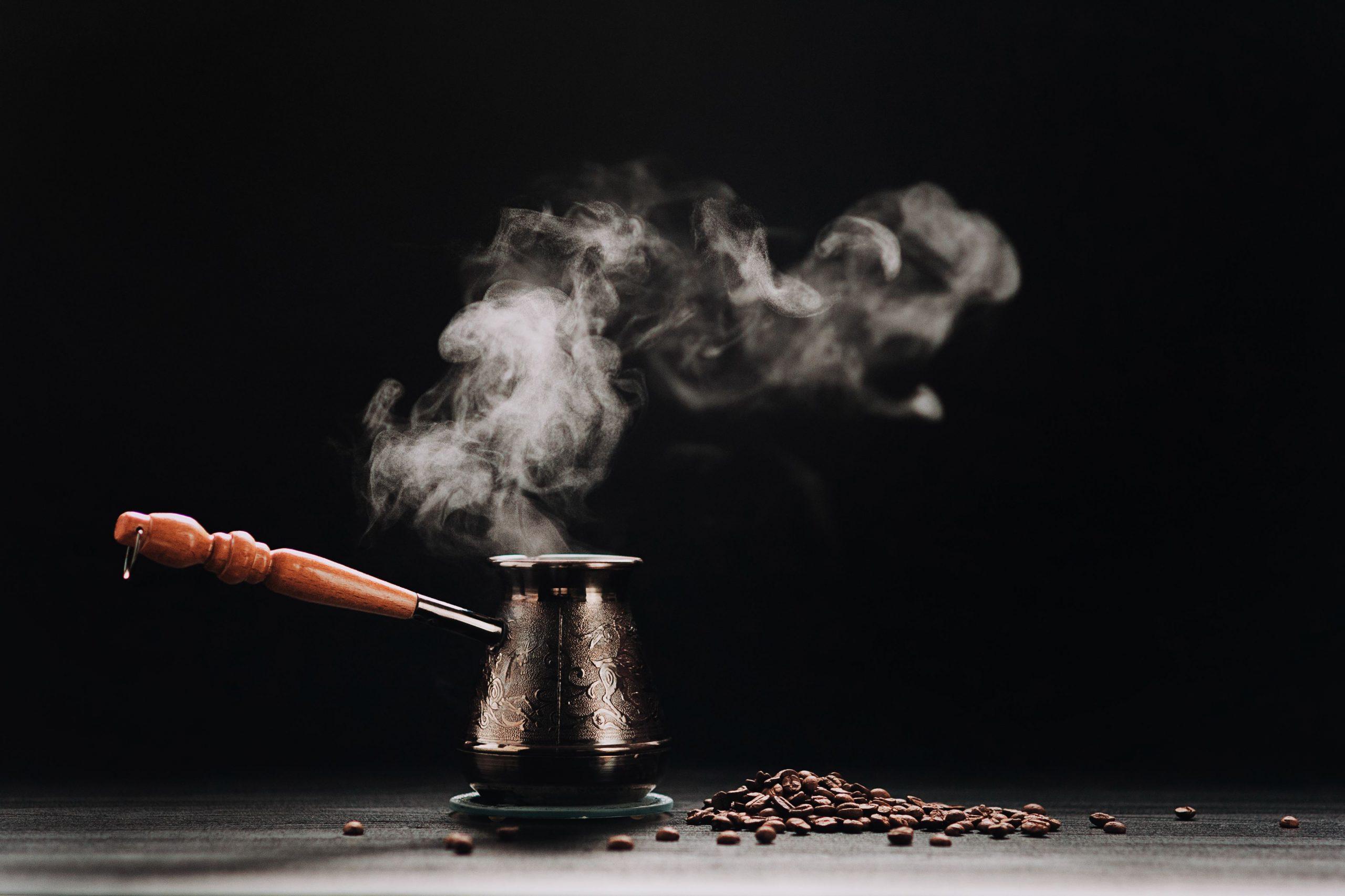турка со свежесваренным кофе с паром